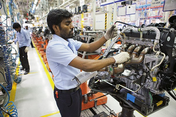 Ford Motor Co. employees assemble engines at the Ford India Pvt. Maraimalai Nagar factory in Chengalpattu, India, on Tuesday, April 17, 2012. Ford's Maraimalai Nagar plant near Chennai in the southern state of Tamil Nadu makes the Figo hatchback, the Fiesta sedan and Endeavour SUV models. Photographer: Kuni Takahashi/Bloomberg via Getty Images